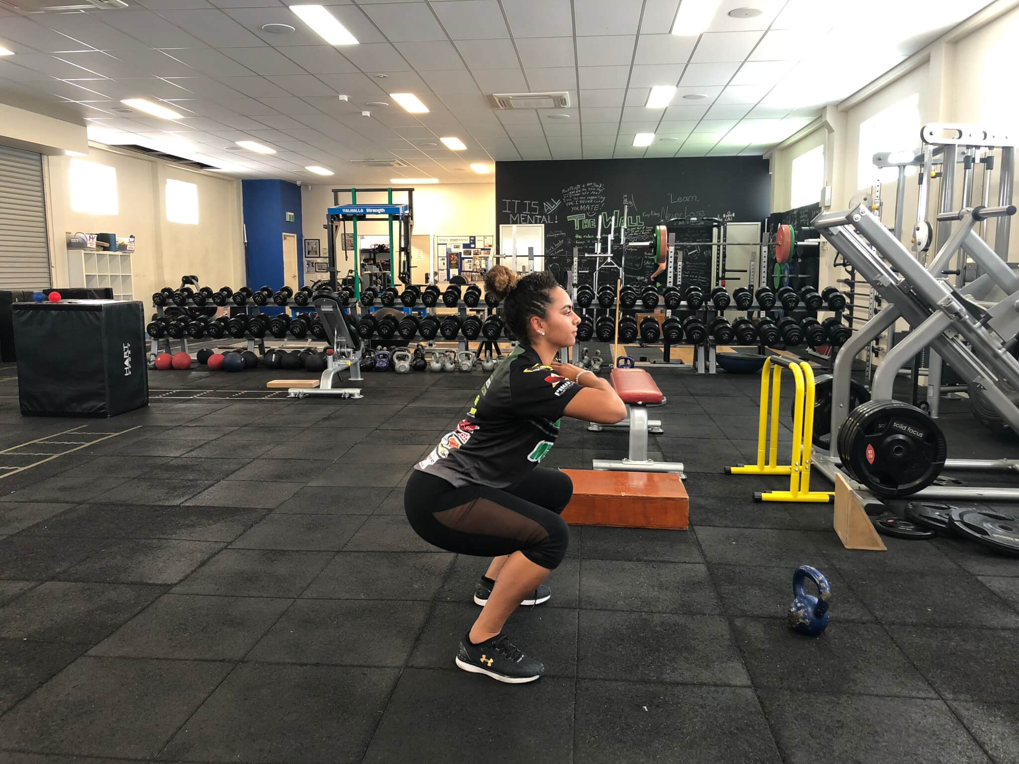 Rachel Warcon demonstrating bodyweight squat technique at Vector Health